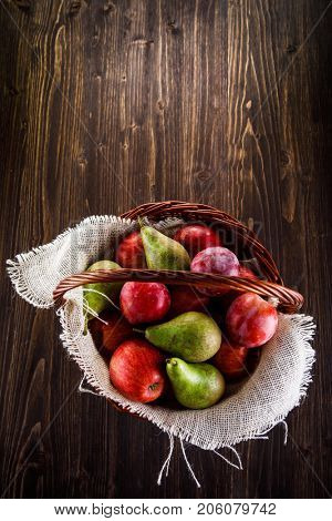 Fruit - apples, pears and plums in wicker basket on wooden table
