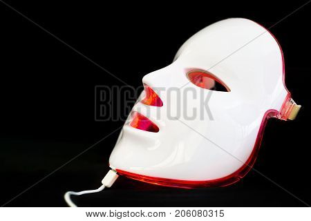 Light rejuvenating mask for facial skin therapy on black background