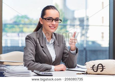 Businesswoman with money sack bag in office