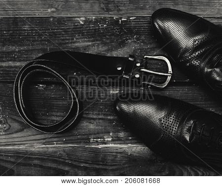 men's leather belt and shoe on wooden table.