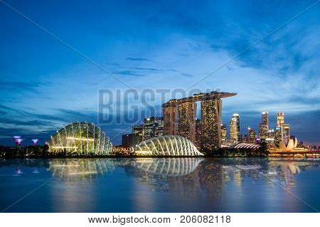 SINGAPORE - SEPTEMBER 8, 2017: Singapore skyline at Marina Bay during sunset blue hour showing Marina Bay Sands and Gardens by the Bay
