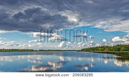 Colorful forest with green yellow trees and raining sky reflected in water surface lake river . Sunny sky with grey clouds. autumn sky after rain.