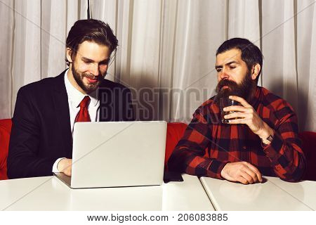 bearded men businessmen long beard brutal caucasian hipster with moustache hold glass with whiskey has smiling face unshaven guys with stylish hair in suit and red tie with laptop