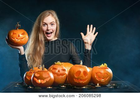Hand countdown - number five. Happy excited smiling woman with Halloween pumpkins over smoky background showing five fingers open palm