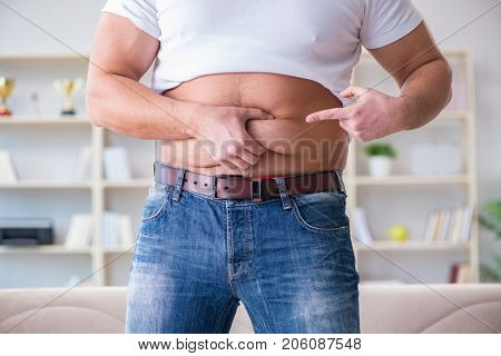 Man suffering from extra weight in diet concept