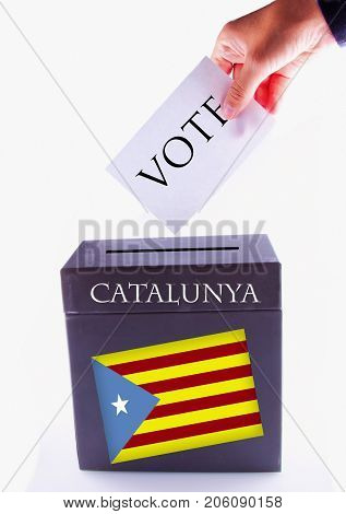 Urn for vote with male hand posting vote and Catalunya banner