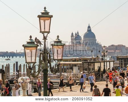 VENICE, ITALY - SEPTEMBER 3, 2013: Visitors on Embankment of the Grand Canal and Basilica di Santa Maria della Salute in the background. Venice, Italy