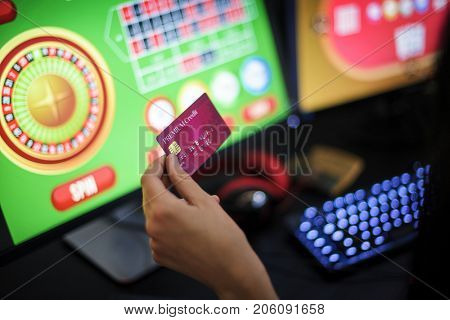 Hand holding credit card playing online gambling
