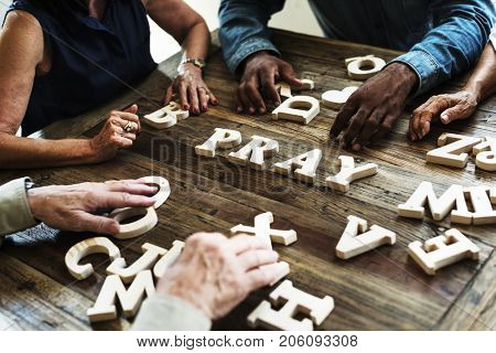 Group of people arrangement a word on wooden table