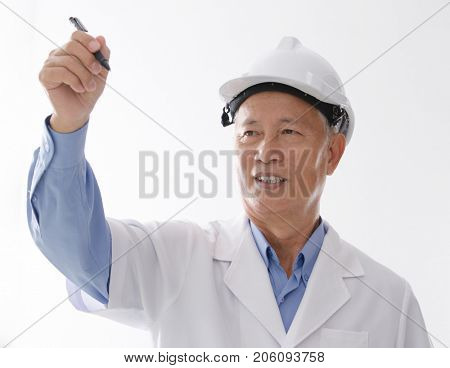 Portrait of Asian engineer with hard hat, hand writing on blank space, standing isolated on white background.