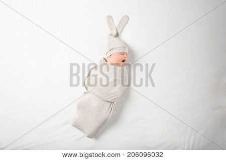 Cute newborn baby in cocoon and funny hat on white background