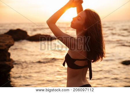 Back view of Enigmatic brunette woman in bikini posing with closed eyes on beach near the sea