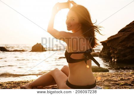 Back view of Pleased brunette woman sitting on beach and making photo on smartphone while looking at the camera