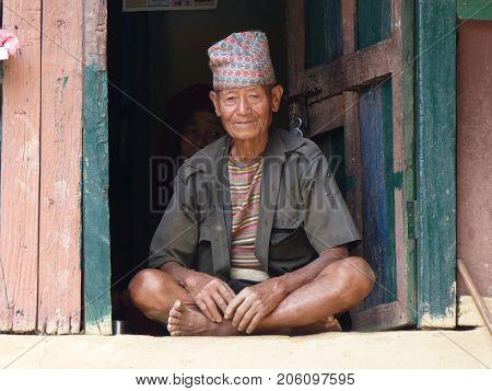 Tallo Chipla Nepal september 7 2015: Old man sitting at doorsill - Meeting local people during Annapurna Circuit trek in Nepal