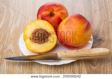 Whole Nectarines, Half Of Nectarine And Knife In Plate