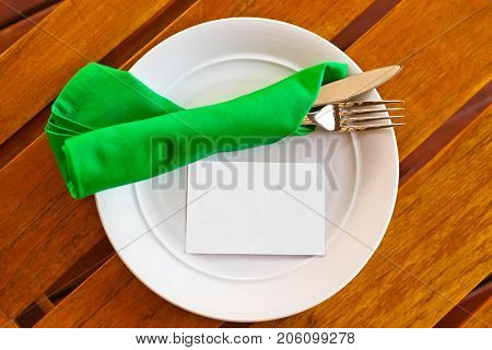 Dishware and blank paper card on table in restaurant - food background