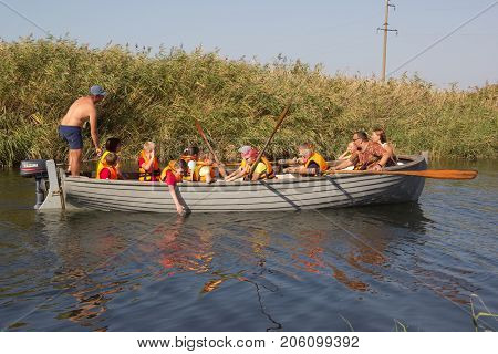 PRIMORSKO-AHTARSK, RUSSIA - SEPTEMBER 15,2017: Schoolchild rowing with oars in a wooden boat on the river in the summer