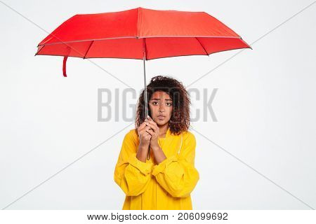 Picture of confused african woman in raincoat hiding under umbrella and looking at the camera over white background