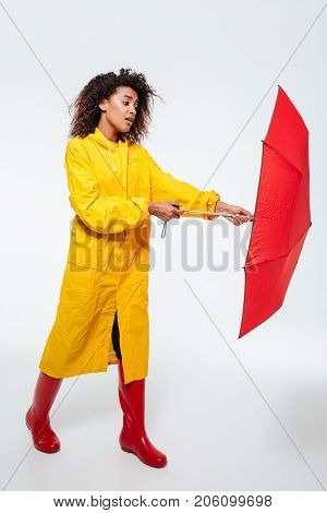 Full length image of confused african woman in raincoat opening umbrella over white background