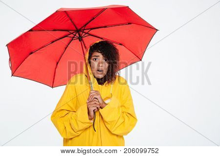 Surprised african woman in raincoat posing with umbrella and looking at the camera over white background
