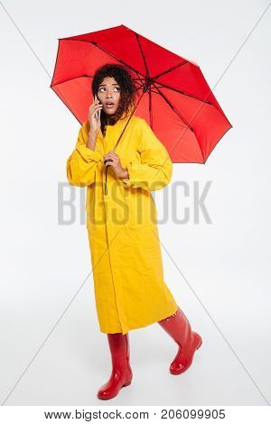 Full length image of confused african woman in raincoat walking with umbrella and talking by the smartphone while looking away over white background
