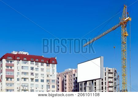 Building Crane Against The Background Of A Multi-storey Building Under Construction. Advertising Bil