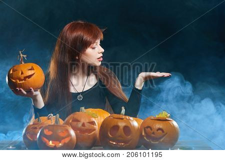 Smiling woman with Halloween pumpkins over smoke background showing open hand palm with copy space