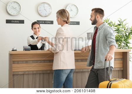 Young couple receiving key from hotel room at reception