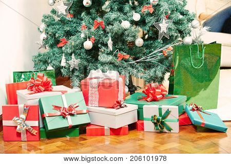 Many gifts laying under christmas tree at christmas eve