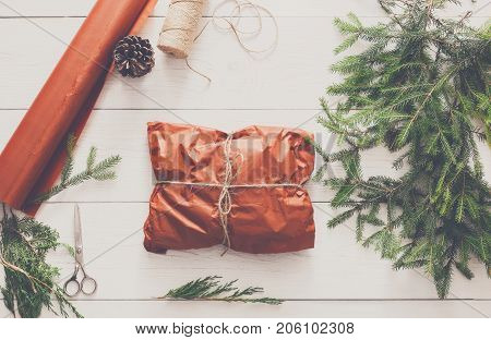 Gift wrapping background. Packaging christmas present in maroon paper decorated with satin ribbon. Winter holidays concept. Top view of white wood table with fir tree branches