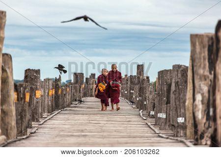 Mandalay, Myanmar - October 1, 2016: Unidentified novices walking on U Bein Bridge near Mandalay in Myanmar.
