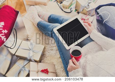 Christmas online shopping. Female buys presents to prepare to xmas eve at tablet with tablet, copy space on screen. Winter holidays sales.