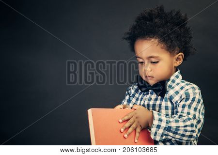 Portrait of a cute little schoolboy with book in hands over blackboard background, elementary school, back to school concept