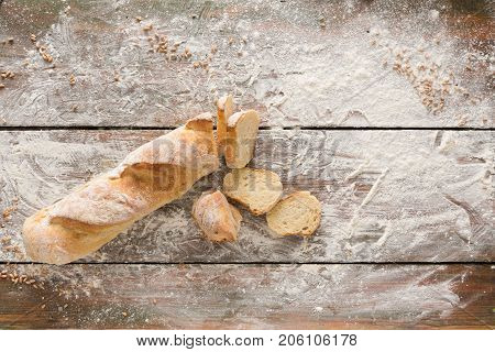 Bakery and grocery background. Cutting baguette, top view on rustic wood