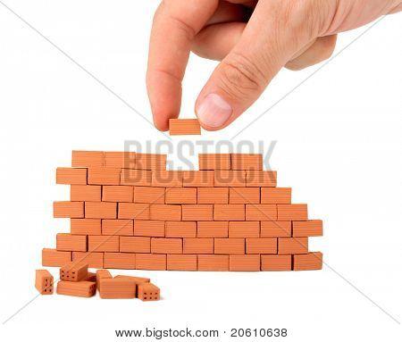Aufbau einer kleinen Mauer auf weißem Hintergrund