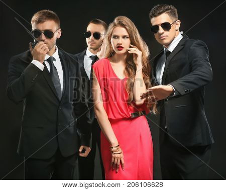 Famous celebrity with bodyguards on dark background
