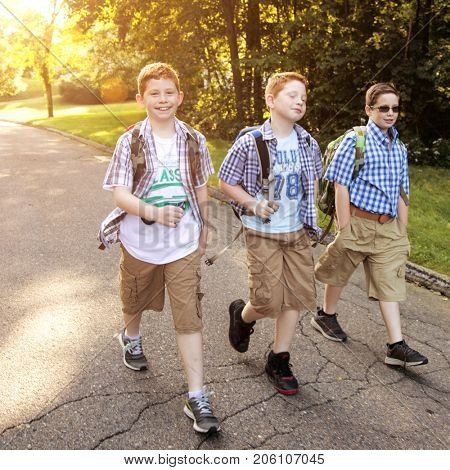 Three boys walking to the morning bus stop