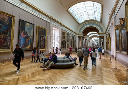 PARIS, FRANCE - JUNE 11, 2017: People looking at paintings in the Louvre Museum. The Louvre is the world's largest museum and a historic monument in Paris, France.