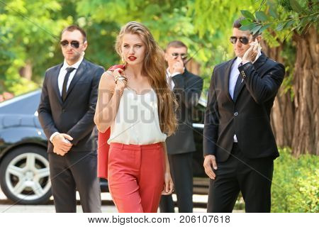 Young businesswoman with bodyguards outdoors