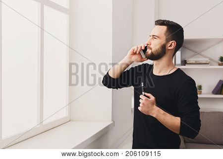 Confident young bearded man vaping electronic cigarette and talking on the mobile phone on white background. Vapor and alternative nicotine free smoking concept, copy space