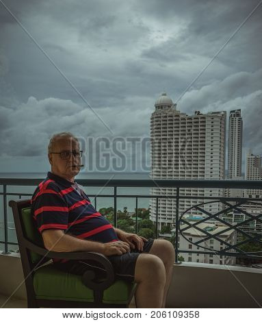 An elderly man smokes a cigar, sitting on the balcony and looking at camera wise eyes. The theme of loneliness and age. The gloomy sky, rainy day
