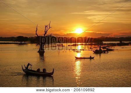 Sunset landscape with boats near famous U Bein bridge near Mandalay in Myanmar