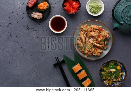 Asian cuisine concept. Beef teriyaki with rice, avocado and ogange salad with seaweed, almond flakes and black sesame and sushi. Set with chopsticks, ginger, soy, wasabi on dark background, copy space