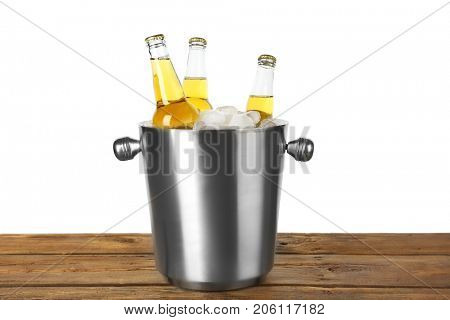 Bottles of lemonade in bucket with ice on wooden table, isolated on white