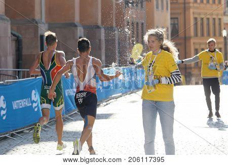 STOCKHOLM - AUG 26 2017: Official giving water bottle to running triathlete Bergere (FRA) in the Men's ITU World Triathlon series event August 26 2017 in Stockholm Sweden