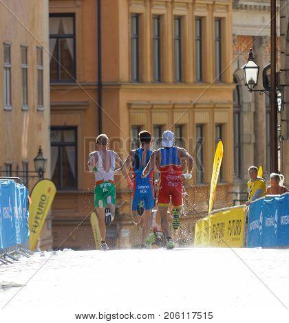 STOCKHOLM - AUG 26 2017: Rear view of running triathlete Hernandez Gundersen and White in the old town in Stockholm in the Men's ITU World Triathlon series event August 26 2017 in Stockholm Sweden