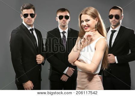 Famous celebrity with bodyguards on grey background