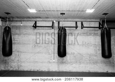 Three black punching bags in the empty boxing gym with naked grunge wall in background black and white