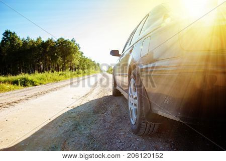 car on empty rural road in sun beam