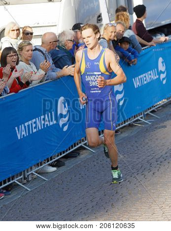 STOCKHOLM - AUG 26 2017: Running triathlete Gabriel Sandor (SWE) at the finish audience clapping hands in the Men's ITU World Triathlon series event August 26 2017 in Stockholm Sweden
